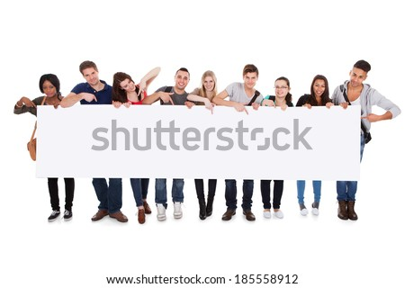 Full length portrait of confident multiethnic college students displaying blank billboard against white background - stock photo