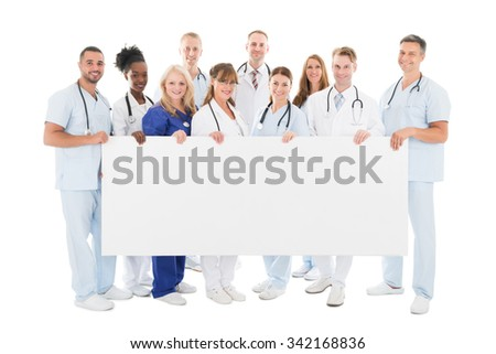 Full length portrait of confident multiethnic medical team holding blank billboard against white background - stock photo