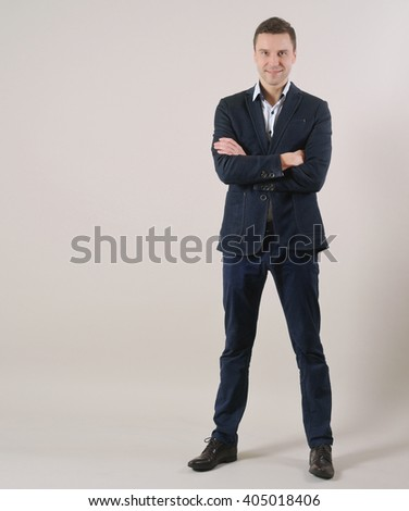 full length portrait of confident smiling businessman standing in suit on grey background; business concept - stock photo