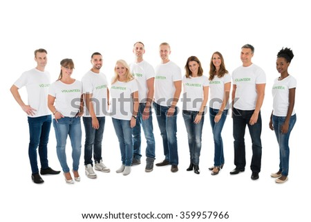 Full length portrait of confident volunteers standing in row against white background