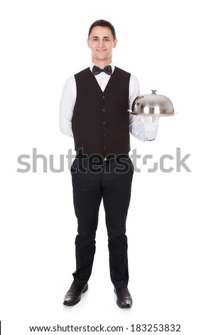 Full length portrait of confident waiter tray with cloche lid cover over white background - stock photo
