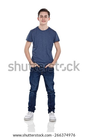 Full length portrait of confident young boy standing with his hands in pocket on white background - stock photo