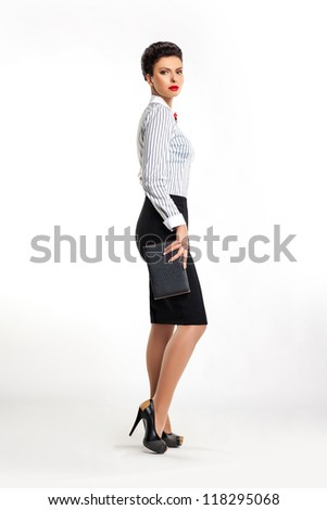 Full length portrait of confident young businesswoman secretary with handbag sideways