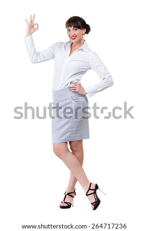 Full length portrait of confident young businesswoman showing OK sign and smiling, over white background - stock photo