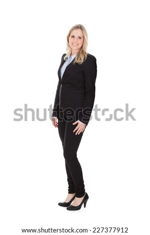 Full length portrait of confident young businesswoman standing over white background - stock photo