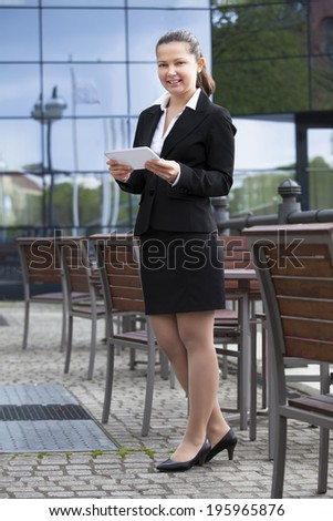 Full length portrait of confident young businesswoman using digital tablet outdoors - stock photo