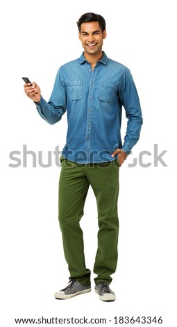 Full length portrait of confident young man using smart phone against white background. Vertical shot. - stock photo