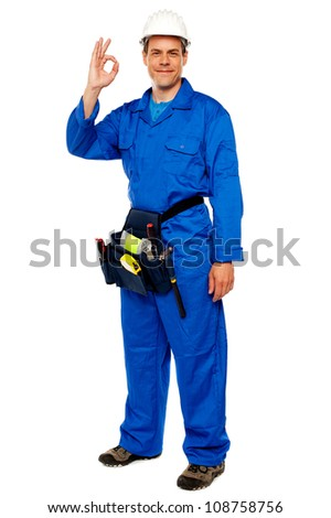 Full length portrait of construction worker gesturing okay sign, carrying tools bag - stock photo