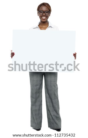 Full length portrait of corporate woman holding blank white billboard - stock photo