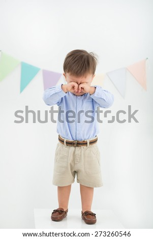 Full-length portrait of crying baby boy rubbing his eyes - stock photo