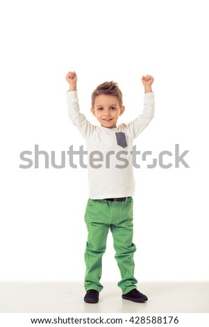 Full length portrait of cute little boy in stylish clothes keeping hands in fists up, looking at camera and smiling, isolated on a white background - stock photo