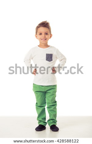 Full length portrait of cute little boy in stylish clothes looking at camera and smiling while standing akimbo, isolated on a white background - stock photo