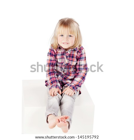 Full length portrait of cute little girl sitting on block isolated over white background - stock photo