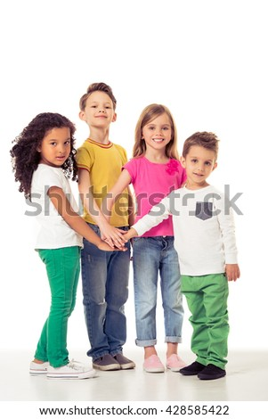 Full length portrait of cute little kids in casual clothes holding hands together, looking at camera and smiling, isolated on a white background
