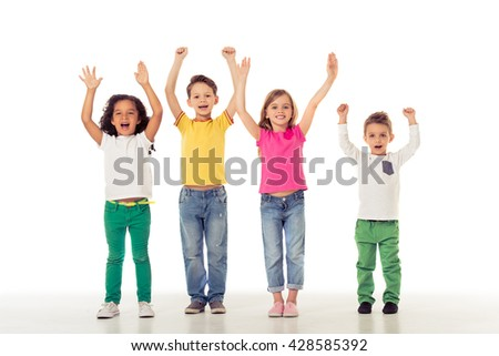 Full length portrait of cute little kids in casual clothes keeping hands up, looking at camera and smiling, isolated on a white background - stock photo