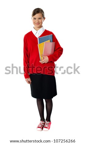 Full length portrait of cute schoolgirl holding books and smiling at camera