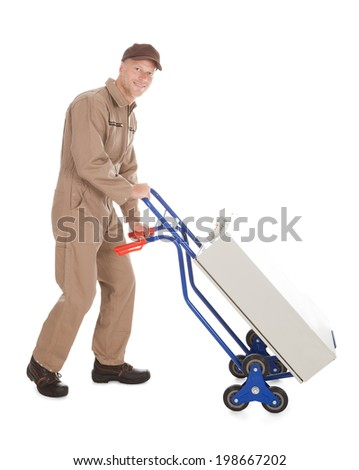 Full length portrait of delivery postman pushing machine on cart over white background - stock photo