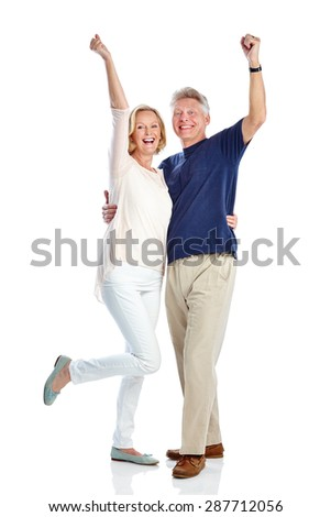 Full length portrait of excited mature couple standing together with their hands raised on white background - stock photo
