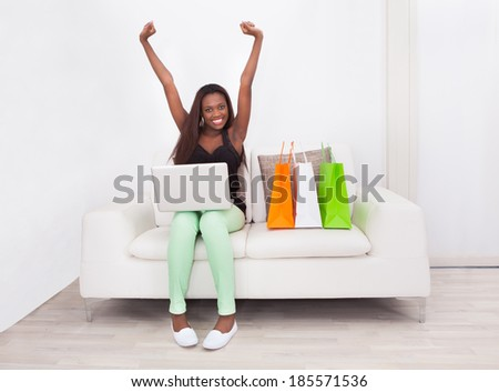 Full length portrait of excited woman shopping online at home - stock photo