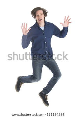Full length portrait of excited young man jumping against white background - stock photo