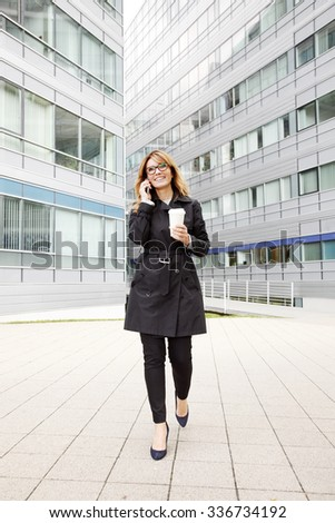 Full length portrait of executive businesswoman walking on the street at financial district.  Professional woman  holding a cup of coffee and making call on her mobile phone after business meeting. - stock photo
