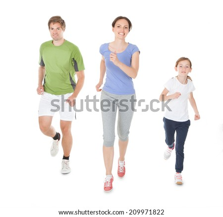 Full length portrait of family in sportswear jogging against white background - stock photo