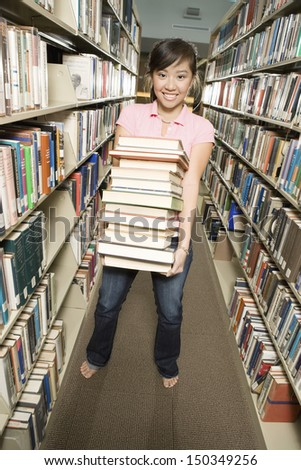Full length portrait of female college student carrying stack of books in the library - stock photo
