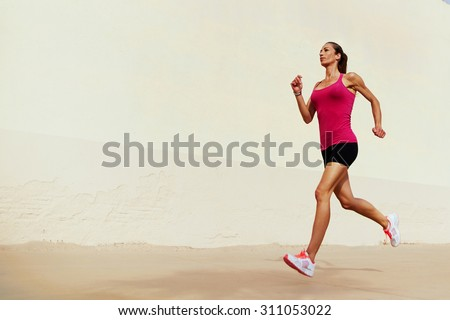 Full length portrait of female runner on morning jog against with copy space area wall for your text message or information, healthy sports woman with sexy figure playing sports outdoors in summer day - stock photo