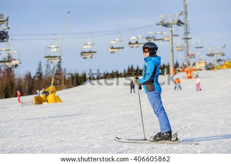 Full length portrait of female skier standing on a ski slope at a sunny day against ski-lift on the background. Winter vacation. Carpathian Mountains, Bukovel - stock photo