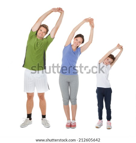 Full length portrait of fit family doing stretching exercise against white background - stock photo