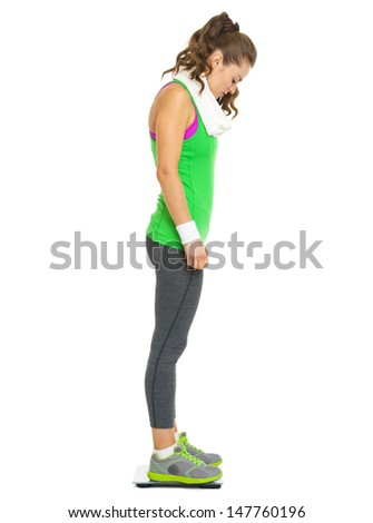 Full length portrait of fitness young woman standing on scales - stock photo