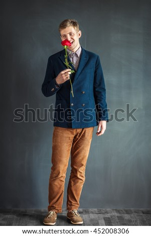 Full length portrait of funny man eating red rose standing against grey wall background - stock photo