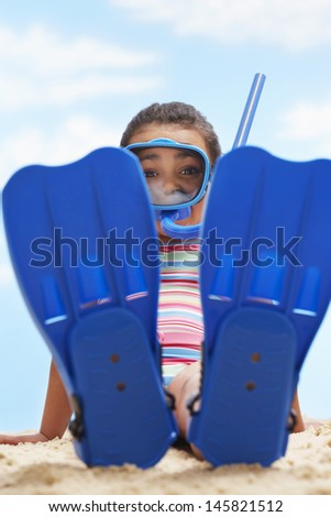 Full length portrait of girl sitting in flippers and snorkeling mask on beach - stock photo