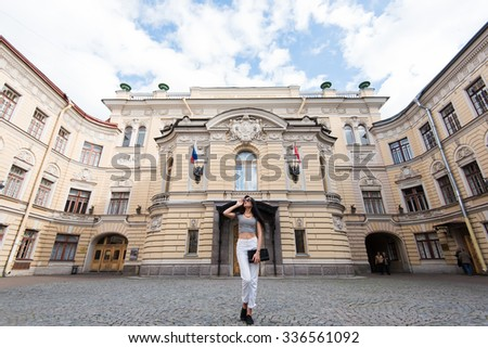 Full length portrait of gorgeous brunette woman posing on the background of beautiful architecture building in Saint Petersburg, young female model rest after city tour and having a good time there  - stock photo