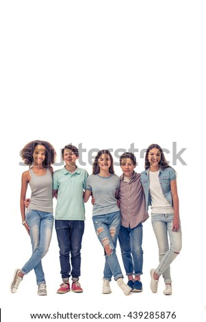 Full length portrait of group of teenage boys and girls hugging, looking at camera and smiling, standing in row, isolated on white - stock photo