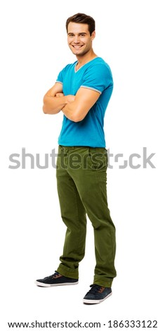 Full length portrait of handsome man in casuals standing arms crossed against white background. Vertical shot. - stock photo