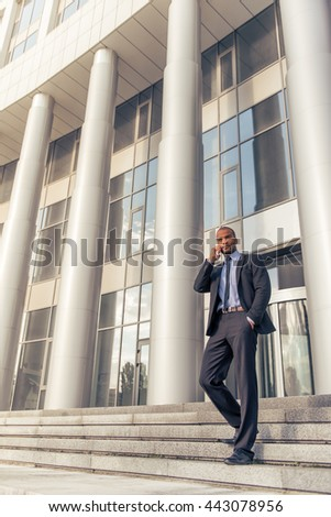 Full length portrait of handsome young Afro American businessman in classic suit talking on the mobile phone, standing outdoors on the stairs of office building - stock photo