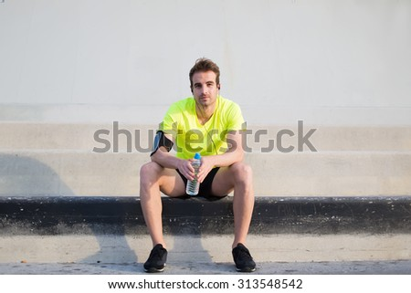 Full length portrait of handsome young sports man sitting on concrete stairs with copy space area on sides while resting after an active run outdoors, male runner in fluorescent bright t-shirt resting - stock photo