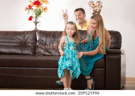 Full length portrait of happy adorable Caucasian family with little girl, father showing victory sign from background, beautiful mother smiling, at home - stock photo