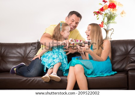 Full length portrait of happy adorable Caucasian family with little girl holding a present sitting on couch at home - stock photo