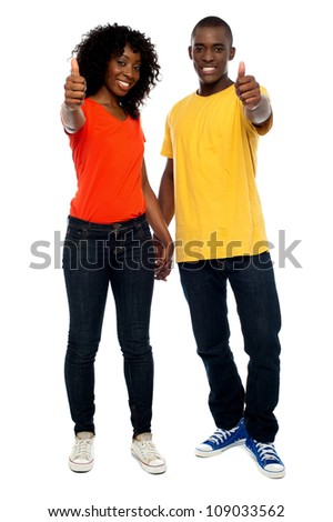 Full length portrait of happy african couple showing thumbs up - stock photo