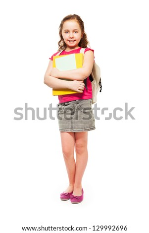 Full length portrait of happy and smiling teenage girl holding pile of books and wearing backpack on white - stock photo