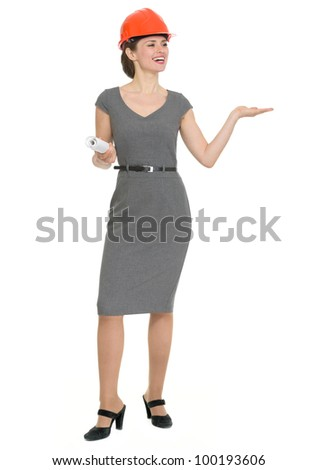 Full length portrait of happy architect woman showing something on empty hand. HQ photo. Not oversharpened. Not oversaturated - stock photo