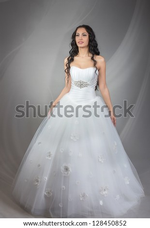 Full length portrait of happy beautiful bride, on grey background - stock photo