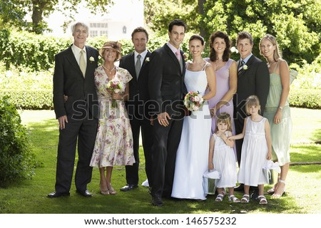 Full length portrait of happy bride and groom standing with guests in garden - stock photo