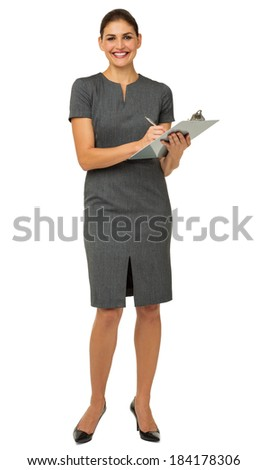 Full length portrait of happy businesswoman holding clipboard and pen against white background. Vertical shot. - stock photo