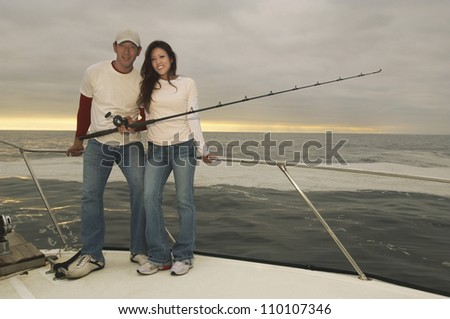 Full length portrait of happy couple fishing on yacht