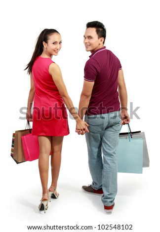 full length portrait of happy couple walking with shopping bag on white background - stock photo