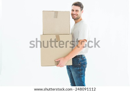 Full length portrait of happy delivery man carrying cardboard boxes on white background - stock photo