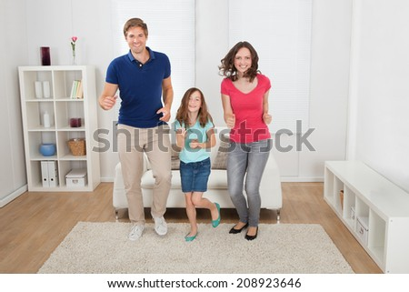 Full length portrait of happy family pretending to run at home - stock photo